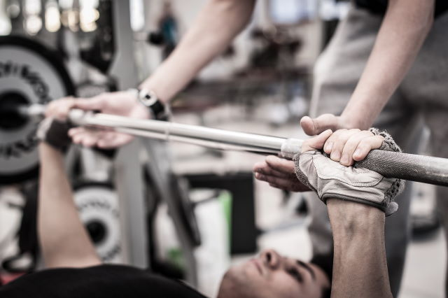 man using weight lifting gloves on bench-press