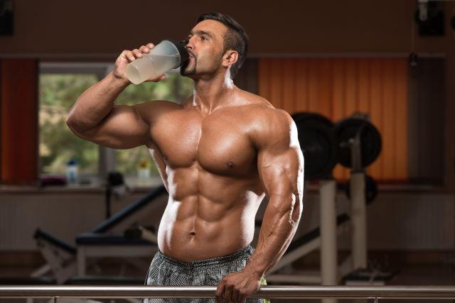 man in gym drinking water
